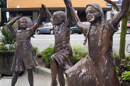 Bronze statue of three girls dancing on Colby Ave in Everett